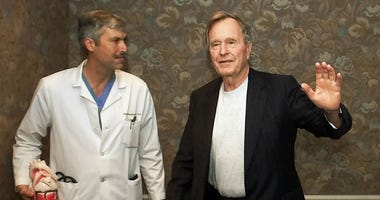 In this Feb. 25, 2000, file photo, former President George H.W. Bush waves as he leaves Methodist Hospital with his cardiologist, Mark Hausknecht, after a news conference in Houston.