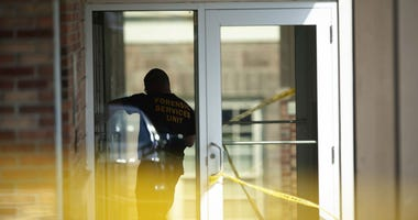 An officer investigates a shooting that occurred in the Masontown borough municipal center on Wednesday, September 19, 2018, in Masontown, Pa.