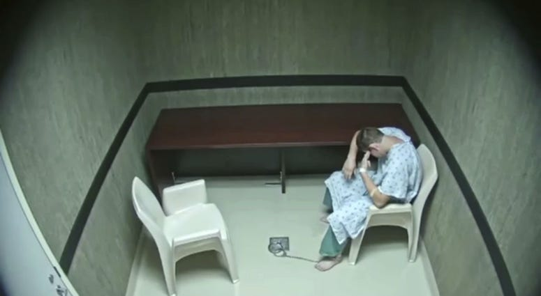 In this image made from video provided on Wednesday, Aug. 8, 2018, by the Broward County Sheriff's Office, Nikolas Cruz points his fingers to his temple at an interrogation room, while officers are out of the room, in Fort Lauderdale, Fla.