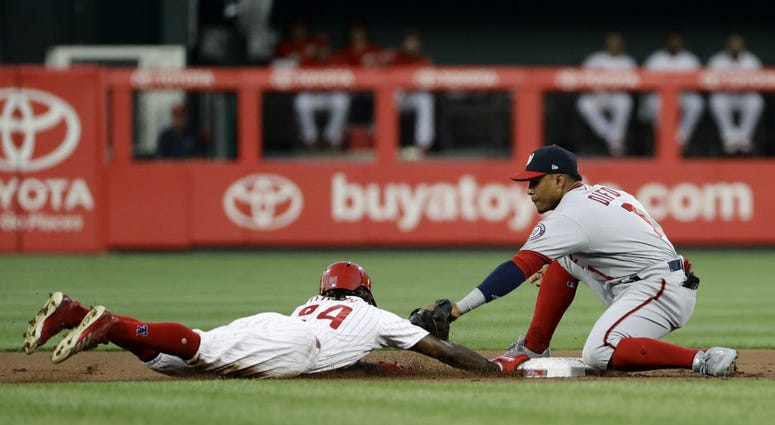 Philadelphia Phillies' Roman Quinn, left, dives safely back to second base under the tag from Washington Nationals shortstop Wilmer Difo on a pickoff attempt during the first inning of a baseball game, Wednesday, Aug. 29, 2018, in Philadelphia.