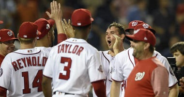 Washington Nationals' Ryan Zimmerman, right center, celebrates his walk-off two-run home run with Michael Taylor (3), Mark Reynolds (14) and others in a baseball game against the Philadelphia Phillies, Wednesday, Aug. 22, 2018, in Washington.