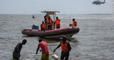 Rescuers search for victims at the site of a capsized cruise boat on Lake Victoria.