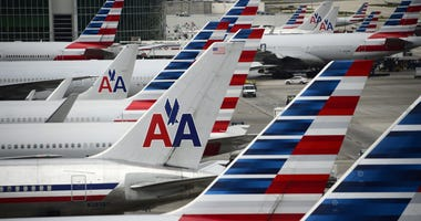 American Airlines planes lined up on the tarmac at an airport.