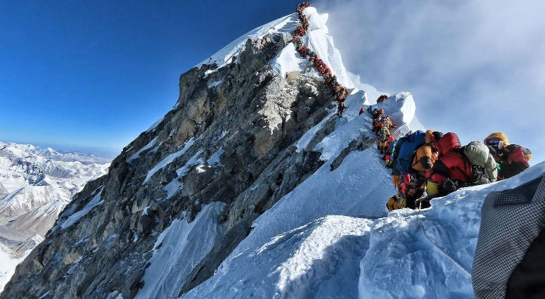 This handout photo taken on May 22, 2019 and released by climber Nirmal Purja's Project Possible expedition shows heavy traffic of mountain climbers lining up to stand at the summit of Mount Everest.