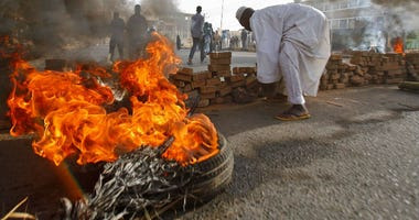 Sudanese protesters block a street with bricks and burning tires as military forces attempted to disperse the ongoing sit-in outside Khartoum's army headquarters on Monday, June 3.