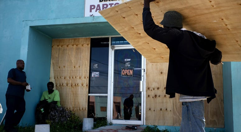 Workers board up a shop's window front as they make preparations for the arrival of Hurricane Dorian in Freeport on August 30.
