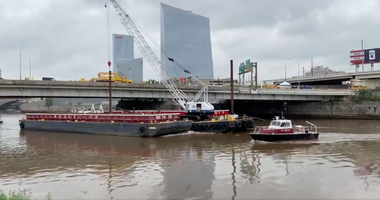 The Army Corps of Engineers use three tugboats to tow the barges that have been stuck by the I-676 bridge.