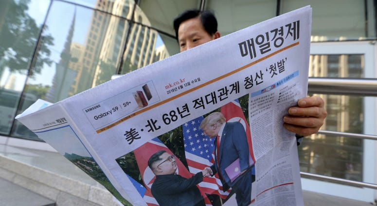 A man reads a newspaper reporting the summit between U.S. President Donald Trump and North Korean leader Kim Jong Un, at a newspaper distributing station in Seoul, South Korea, Tuesday, June 12, 2018.