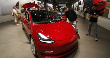 In this July 6, 2018, file photo prospective customers confer with sales associates as a Model 3 sits on display in a Tesla showroom in the Cherry Creek Mall in Denver.