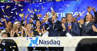 In this July 19, 2018, file photo Brendan Kennedy, third from right in front, CEO and founder of British Columbia-based Tilray Inc., a major Canadian marijuana grower, leads cheers as confetti falls to celebrate his company's IPO.