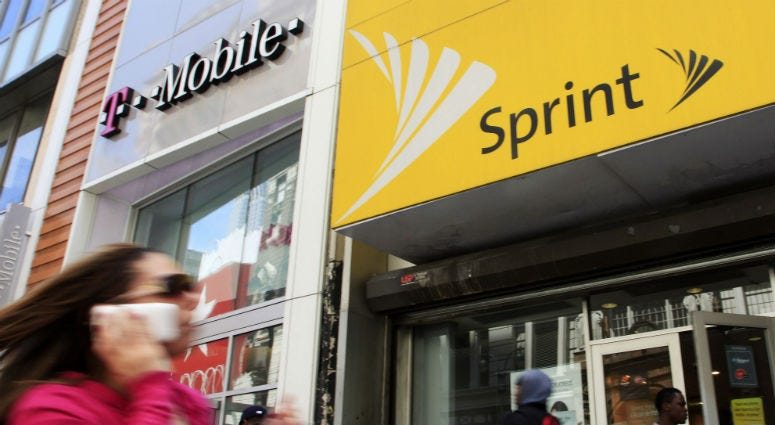 Woman walks past T-Mobile and Sprint stores in New York