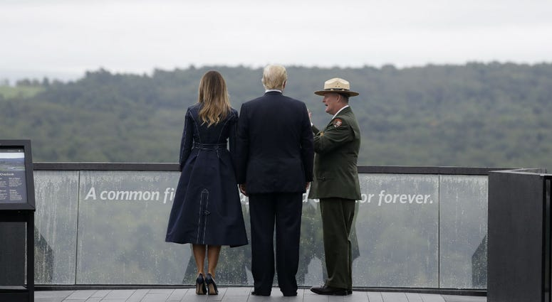 President Donald Trump and first lady Melania Trump, escorted by Stephen Clark, Superintendent of the National Parks of Western Pennsylvania, walk along the September 11th Flight 93 memorial, Tuesday, Sept. 11, 2018, in Shanksville, Pa.