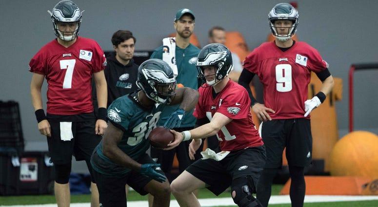 Philadelphia Eagles quarterback Carson Wentz (11) hands off to running back Matt Jones (38) in front of quarterback Nick Foles (9) and quarterback Nate Sudfeld (7) during organized team activities.