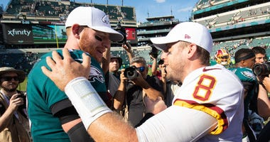 Philadelphia Eagles quarterback Carson Wentz (11) and Washington Redskins quarterback Case Keenum (8) shake hands on the field after the game at Lincoln Financial Field.