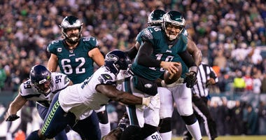 Philadelphia Eagles quarterback Josh McCown (18) tackled by Seattle Seahawks defensive end Jadeveon Clowney (90) and defensive end Jarren Reed (91) during the fourth quarter in a NFC Wild Card playoff football game at Lincoln Financial Field.