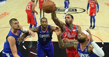 Los Angeles Clippers center Ivica Zubac (40) forward Kawhi Leonard (2), and Marcus Morris Sr. (31) and Philadelphia 76ers forward Mike Scott (1) reach for a rebound in the second half of the game at Staples Center.