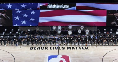 NBA: Utah Jazz at New Orleans Pelicans Members of the New Orleans Pelicans and Utah Jazz kneel together around the Black Lives Matter logo on the court during the national anthem before the start of an NBA basketball game.