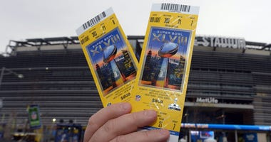 A fan holds up tickets outside the stadium before in Super Bowl XLVIII at MetLife Stadium.