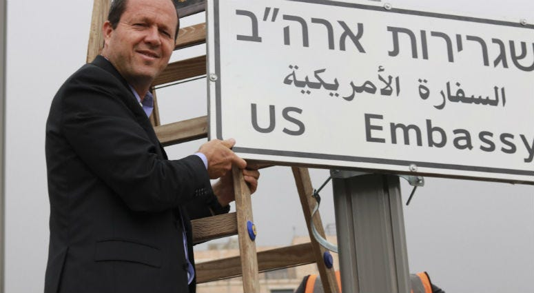 Jerusalem Mayor Nir Barkat poses with a new road sign to the new U.S. Embassy in Jerusalem