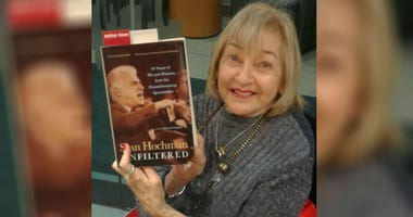 "Gloria Hochman holding the book ""Stan Hochman Unfiltered: 50 Years of Wit and Wisdom from the Groundbreaking Sportswriter."""