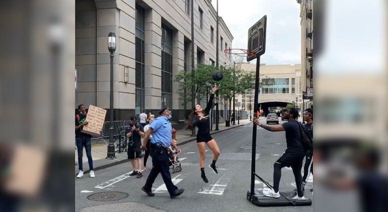 Stephania Ergemlidze playing basketball with a police officer