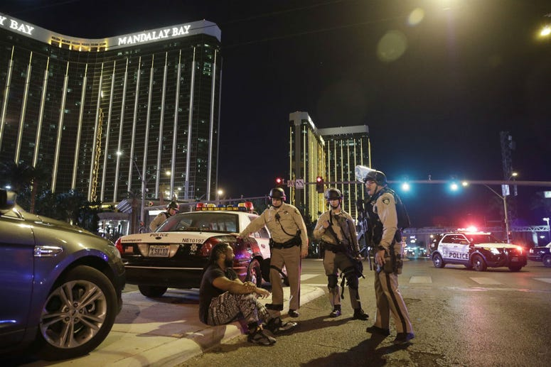 In this Oct. 1, 2017 file photo, police officers stand at the scene of a mass shooting near the Mandalay Bay resort and casino on the Las Vegas Strip, in Las Vegas.