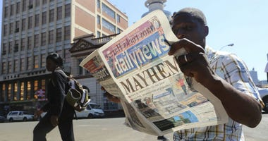 A man reads a newspaper headline in Harare, Zimbabwe,Wednesday, Aug, 2, 2018.