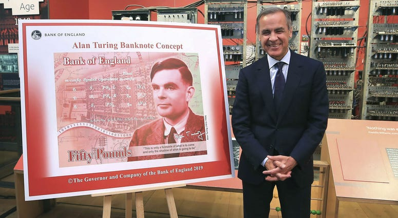 Governor of the Bank of England, Mark Carney poses for a photo with the artwork for the concept of the new 50 pound notes, after announcing that Second World War code-breaker Alan Turing has been selected to feature on the new notes.