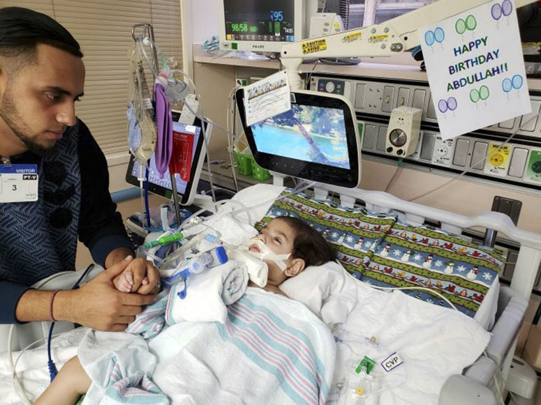 Ali Hassan is shown with his dying 2-year-old son Abdullah in a Sacramento hospital.