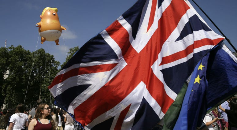 An EU and a British union flag are displayed in front of a six-meter high cartoon baby blimp of U.S. President Donald Trump, as it is flown as a protest against his visit, in Parliament Square in London, England, Friday, July 13, 2018.