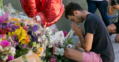 Paolo Singer, 27, a Silver Lake resident, prays at a makeshift memorial of flowers, candles and notes growing on the sidewalk outside the Silver Lake Trader Joe's store in Los Angeles, Monday, July 23, 2018.