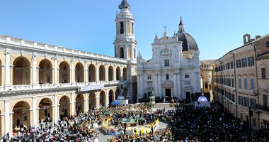 Pope Francis seen on a giant screen at right, celebrates Mass outside Loreto's cathedral, central Italy, Monday, March 25, 2019.