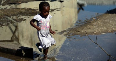 A young girl walks into the water outside a school setup as a displacement center at Inhamizua, outside of Beira, Mozambique, Tuesday, March 26, 2019.