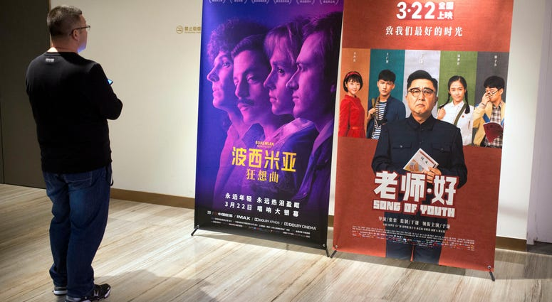 """A customer looks at a movie poster for the film """"Bohemian Rhapsody"""" at a movie theater in Beijing, Wednesday, March 27, 2019."""
