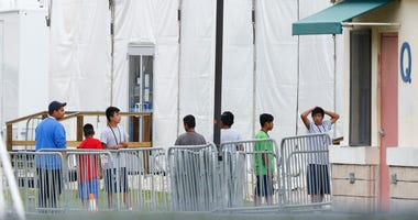 FILE - In this June 20, 2018, file photo, immigrant children walk in a line outside the Homestead Temporary Shelter for Unaccompanied Children, a former Job Corps site that now houses them in Homestead, Fla.  The Trump administration wants up to two years