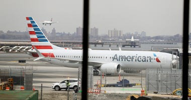 FILE - In a March 13, 2019 file photo, an American Airlines Boeing 737 MAX 8 sits at a boarding gate at LaGuardia Airport in New York. American Airlines said Sunday, April 7, 2019 it is extending by over a month its cancellations of about 90 daily flights