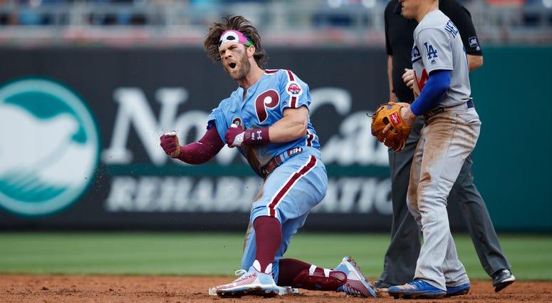 Philadelphia Phillies' Bryce Harper, left, celebrates past Los Angeles Dodgers shortstop Enrique Hernandez after hitting an RBI-single during the eighth inning of a baseball game, Thursday, July 18, 2019, in Philadelphia. Philadelphia won 7-6.