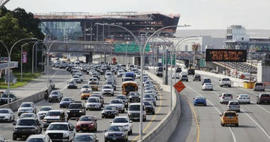 In this Aug. 1, 2018, photo, cars on the Grand Central Parkway pass LaGuardia Airport in New York. The Trump administration has proposed rolling back tougher Obama-era gas mileage requirements that are set to take effect after 2020.