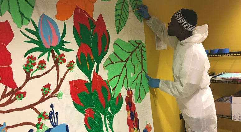 Belo, 25, paints a section of a mural as part of a Mural Arts same-day pay program.