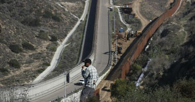 A man looks out at the U.S. border where workers are replacing parts of the U.S. border wall for a higher one, in Tijuana, Mexico, Wednesday, Dec. 19, 2018.