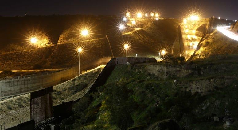 Floodlights from the U.S, illuminate multiple border walls Monday, Jan. 7, 2019, seen from Tijuana, Mexico.