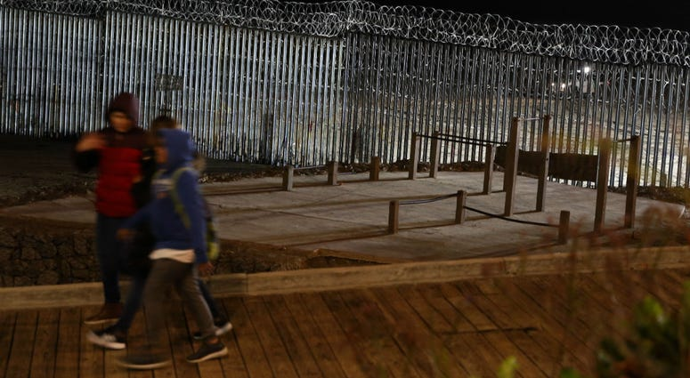 Floodlights from the U.S, illuminate the border wall, topped with razor wire, as a people pass Monday, Jan. 7, 2019, at the beach in Tijuana, Mexico.