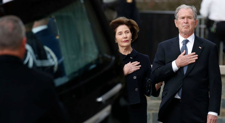 Former President George W. Bush and former first lady Laura Bush watch as the flag-draped casket of former President George H.W. Bush is carried by a joint services military honor guard to a State Funeral at the National Cathedral December 5, 2018.