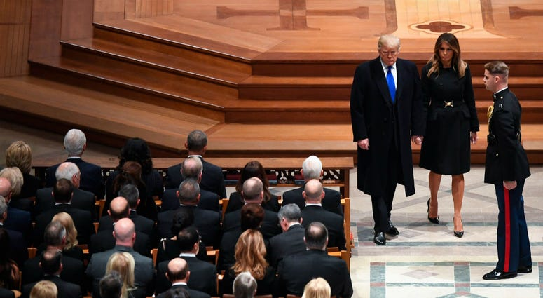 President Donald Trump and first lady Melanie Trump arrive as former President George H.W. Bush is honored with a state funeral at the Washington National Cathedral.