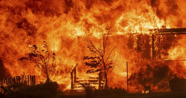 Flames consume a home as the River Fire tears though Lakeport, Calif., on Tuesday, July 31, 2018.