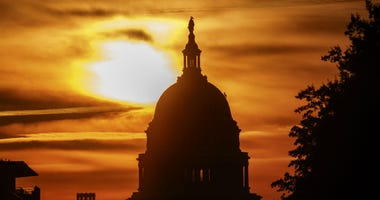 The rising sun silhouettes the U.S. Capitol dome at daybreak in Washington.
