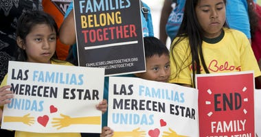 In this June 1, 2018, file photo, children hold signs during a demonstration in front of the Immigration and Customs Enforcement offices in Miramar, Fla.