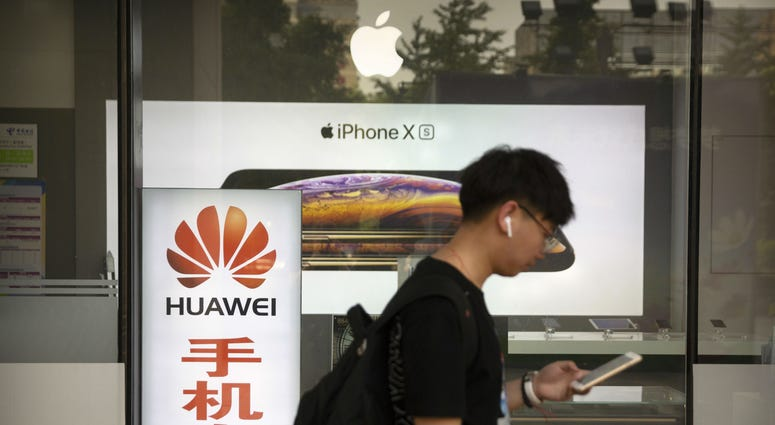 A man looks at his smartphone as he walks past an electronics shop advertising phones from Huawei and Apple in Beijing, Friday, May 24, 2019.