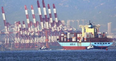 In this Oct. 8, 2018, photo, tugboats move a container ship to the dockyard of a seaport in Qingdao in eastern China's Shandong province.