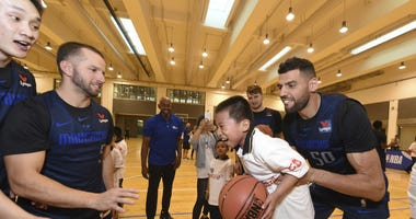 In a photo provided by NBAE, Dallas Mavericks center Salah Mejri, of Tunisia, lifts a participant during the NBA Cares Special Olympics Basketball Clinic, Thursday, Oct. 4, 2018, at Oriental Sports Center in Shanghai.